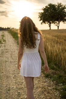Young woman walking on field path, evening sun - SARF002056