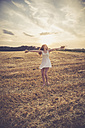 Young woman standing on barley field in the evening, straw in the hands - SARF002050