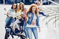 Teenage girl showing thumbs up while her friends with scooter waiting at background - CHAF000783