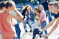 Four female friends with shopping cart spending their time together - CHA000790