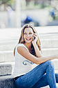Portrait of smiling teenage girl telephoning with smartphone - CHAF000788