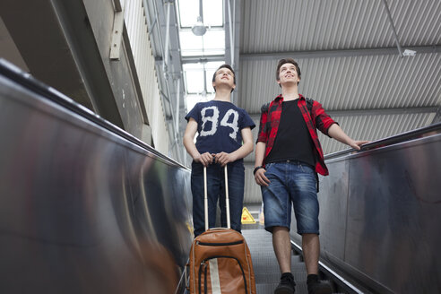 Two teenage boys with baggage standing on an escalator - MMFF000852