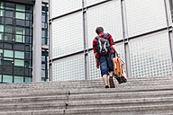 Germany, Berlin, teenage boy with  suitcase walking upstairs - MMFF000876