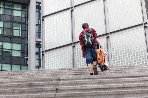 Germany, Berlin, teenage boy with  suitcase walking upstairs - MMFF000876