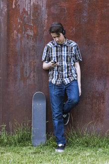 Teenage boy with skateboard leaning on corten wall hearing music - MMFF000860