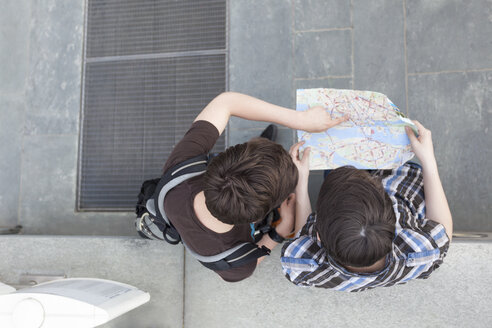 Germany, Berlin, two teenage boys looking at city map - MMFF000867