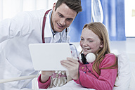 Doctor and girl looking at digital tablet in a hospital room - ZEF006020