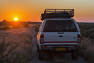 Botswana, Kalahari, Central Kalahari Game Reserve, off-road vehicle on a piste at sunrise - FO008269