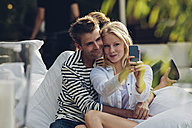 Young woman taking a selfie of herself and her boyfriend in an outdoor cafe - CHAF000957