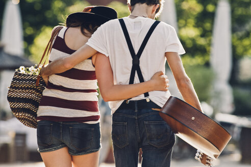 Back view of young couple in love walking arm in arm - CHAF000780