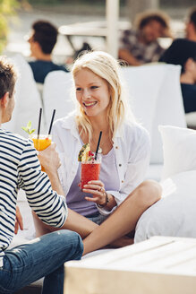 Portrait of happy young woman with glass of fresh juice sitting in a pavement cafe with her boyfriend - CHAF000810