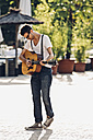 Young man playing guitar on the street - CHAF000816