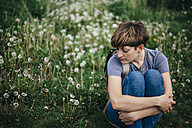 Portrait of young woman sitting on a meadow hugging knees - DWF000242