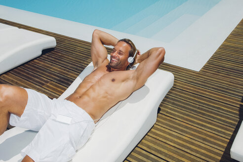 Smiling man with headphones lying at pool edge - CHAF000616