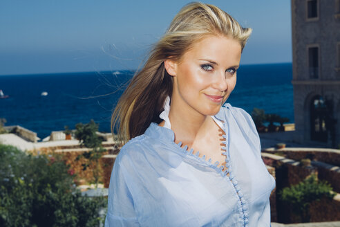 Spain, Majorca, portrait of smiling blond woman at the coast - CHAF000621