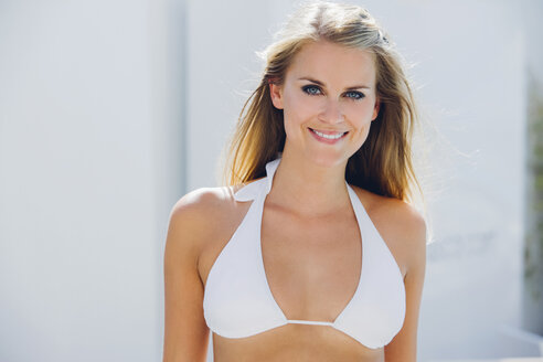 Portrait of smiling blond woman wearing bikini top - CHAF000626