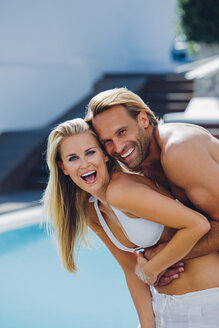 Portrait of happy young couple having fun at poolside - CHAF000632
