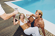 Couple at pool edge receiving drinks from waiter - CHA000970
