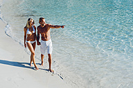 Spain, Majorca, couple walking on the beach with man pointing finger - CHAF000664