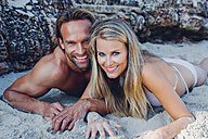 Smiling couple lying on the beach - CHAF000670