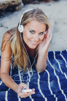 Smiling woman relaxing and listening music on the beach - CHAF000966