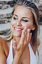 Woman applying sunscreen lotion on her face - CHAF000675