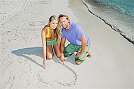 Couple in love on beach drawing heart in sand - CHAF000686