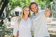 Smiling couple outdoors with man pointing finger - CHAF000689