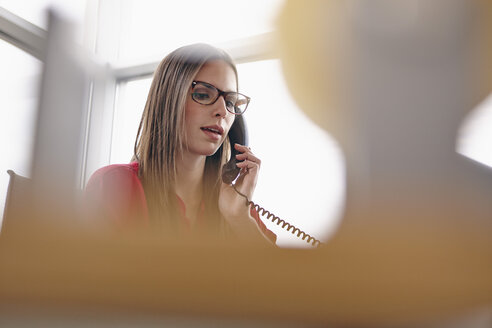 Young woman in office on the phone - RHF000941