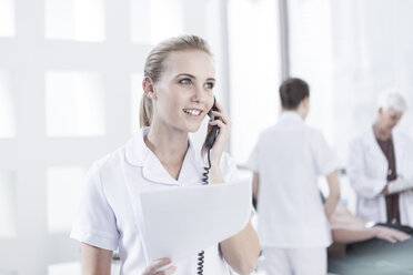 Nurse in hospital with documents on the phone - ZEF005978