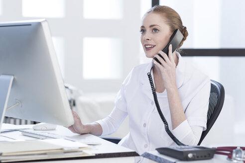 Nurse at desk on the phone - ZEF006048