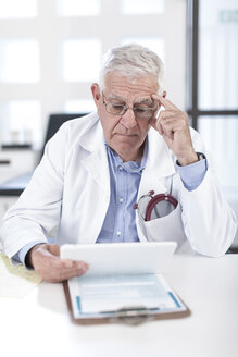 Serious senior doctor at desk looking at patient file - ZEF006750