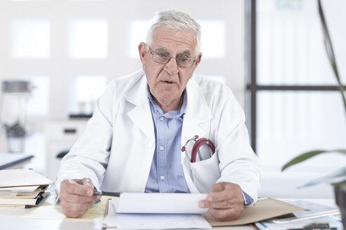 Serious senior doctor sitting at desk - ZEF005999