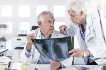 Two doctors at desk discussing x-ray - ZEF006054