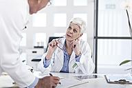 Two doctors talking at desk - ZEF006055