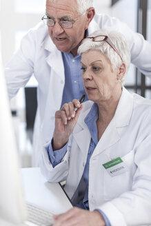 Two doctors talking at desk - ZEF006060