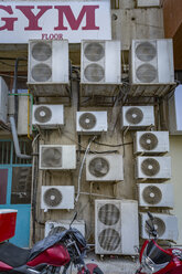 UAE, Dubai, several air conditioning units on a wall in a back road - NKF000309