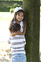 Portrait of smiling girl leaning on a tree hugging her little brother - GDF000812