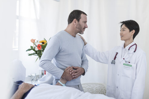 Doctor consoling man visiting patient in hospital - ZEF006765