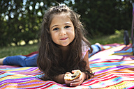 Portrait of smiling little girl lying on a blanket - GDF000819