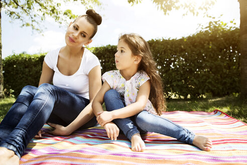 Mother and her little daughter sitting on a blanket - GDF000828