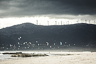 Spain, Andalusia, Tarifa, Kiter in front of mountain with wind wheels - KBF000340