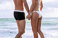 USA, Miami, young couple holding hands in front of the sea - CHAF000833