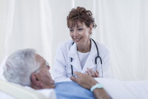Doctor visiting senior patient in hospital bed - ZEF006831