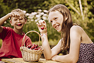 Girl and boy enjoying cherries in garden - MFF001880