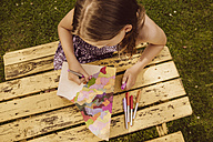 Girl drawing on a wooden magazine file in garden - MFF001887
