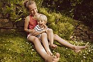 Girl tickling little boy in garden - MFF001890