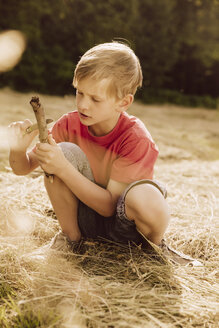 Boy carving a piece of wood on field - MFF001952