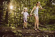 Little boy and girl balancing on fallen tree in forest - MFF001926