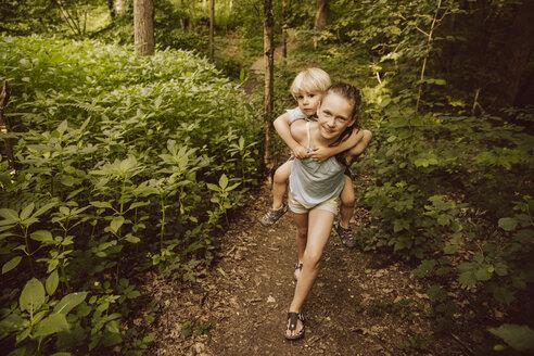 Girl carrying little boy piggyback through a forest - MFF001934